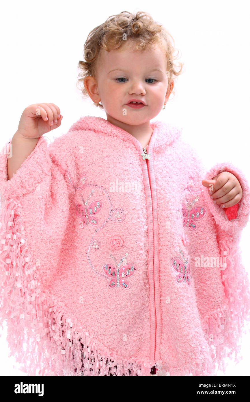 Lovely baby girl walking in pink poncho looking like an