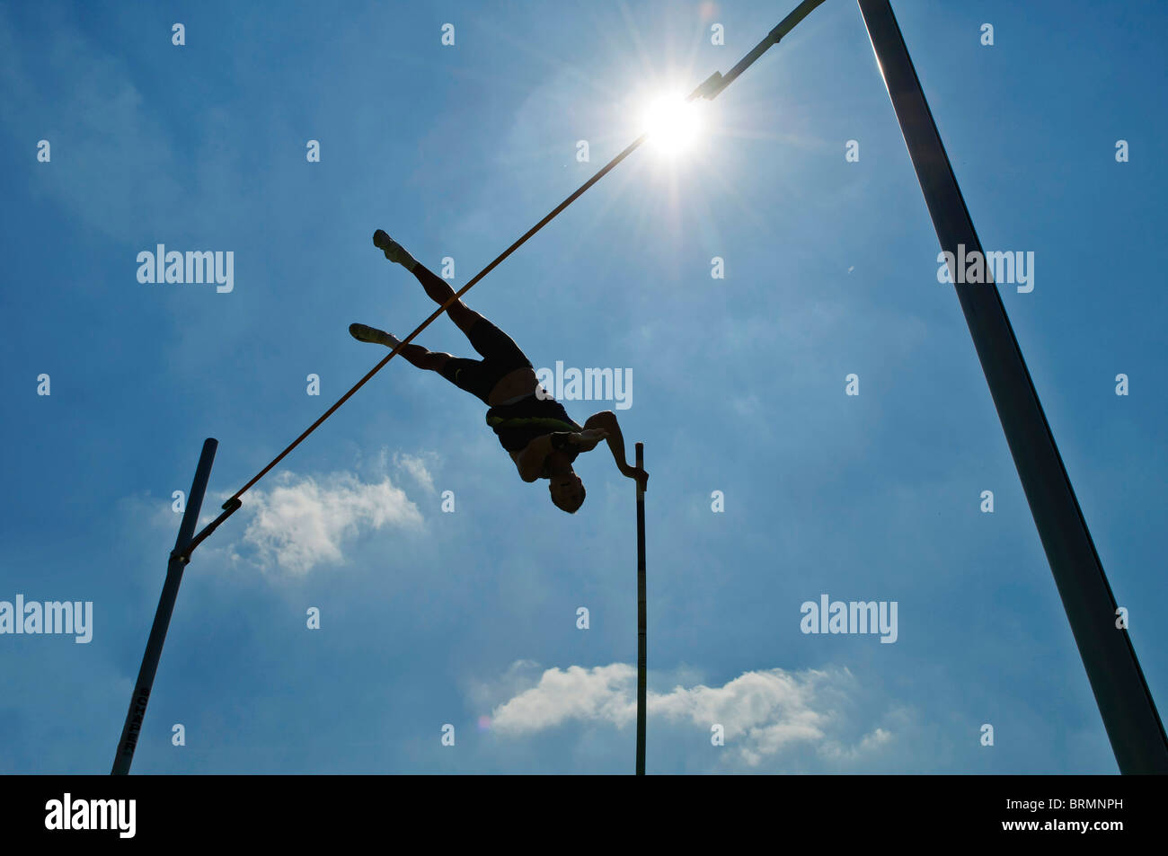 Pole Vaulter makes the jump against blue sky - Stock Image