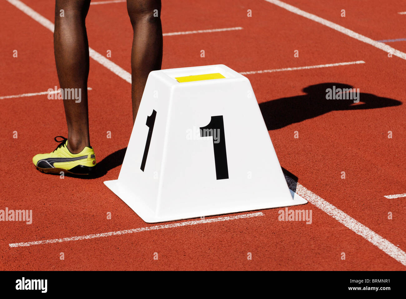 legs of a male sprinter next to starting block number one on athletic track outside - Stock Image
