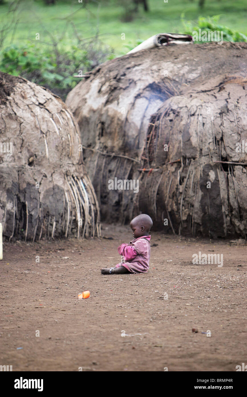 Maasai baby sitting on the ground among  dome-shaped mud huts - Stock Image