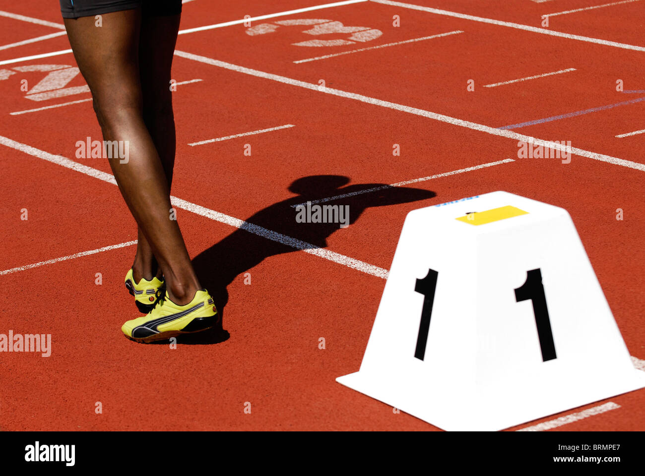 legs of a male sprinter next to starting block number one on athletic track outside Stock Photo