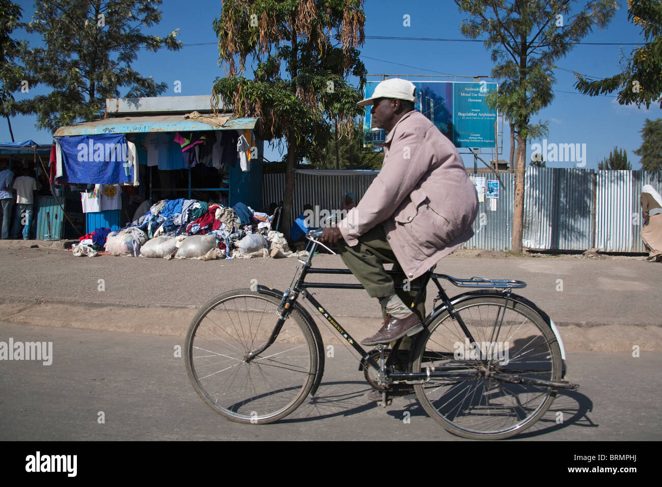 Man riding a bicycle past a roadside stall in Awassa - Stock Image