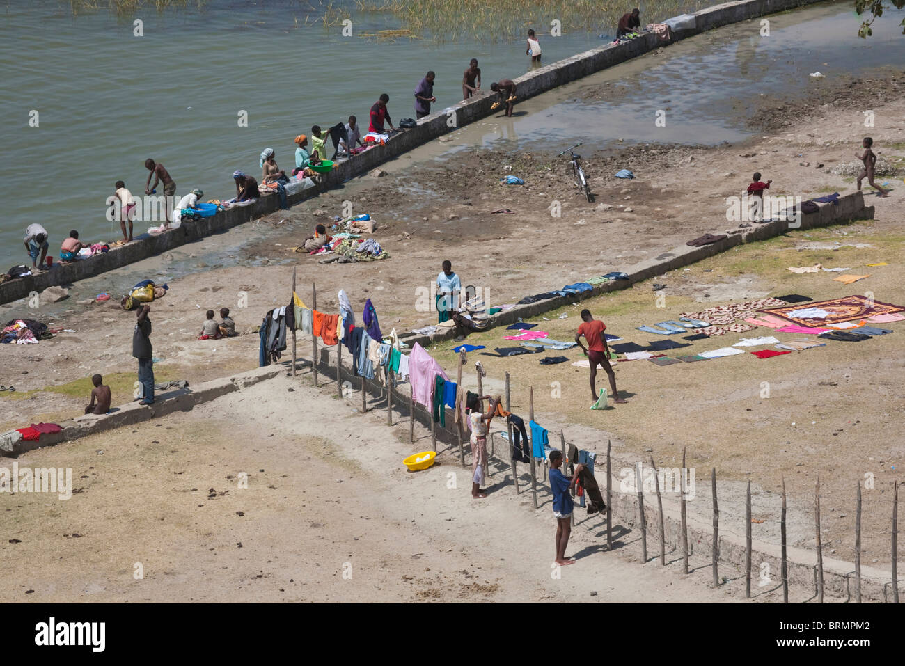 Locals gathered at Lake Awassa to do their washing with colourful garments hanging on a fence to dry - Stock Image