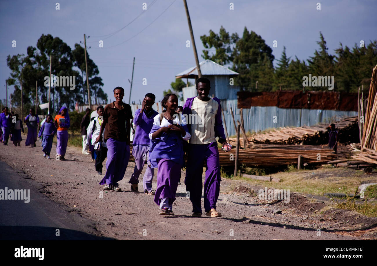 Scholars in purple uniforms walking on the roadside as they walk home from school on the outskirts of Addis Ababa - Stock Image
