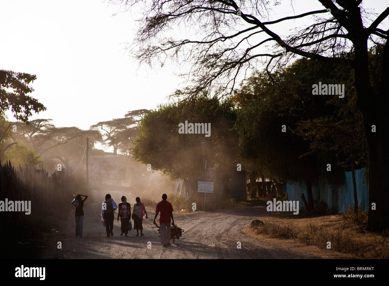 Local people walking to work on a dusty road in Awassa - Stock Image