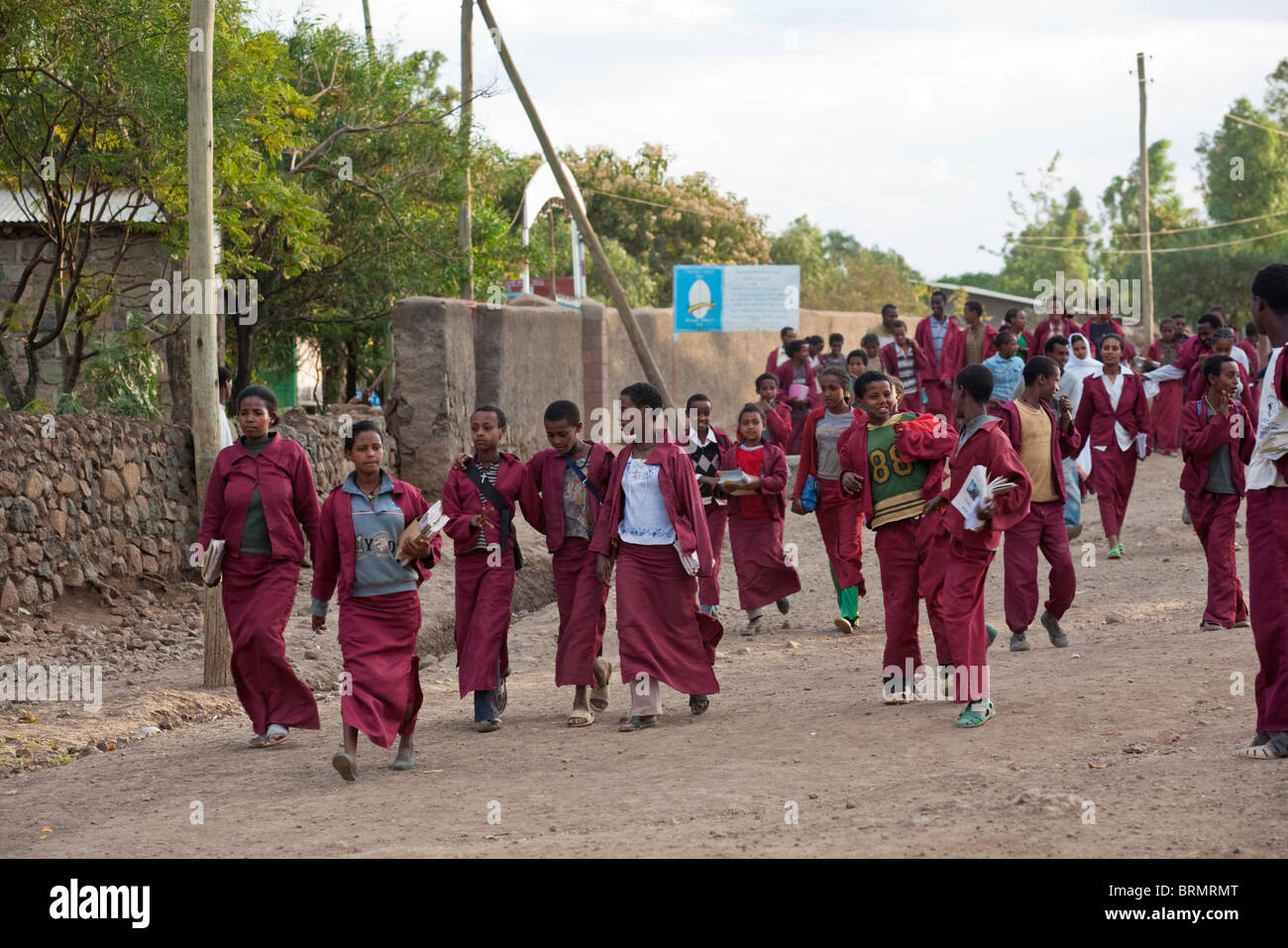 School children dressed in red uniforms going home after school has finished in Lalibela - Stock Image