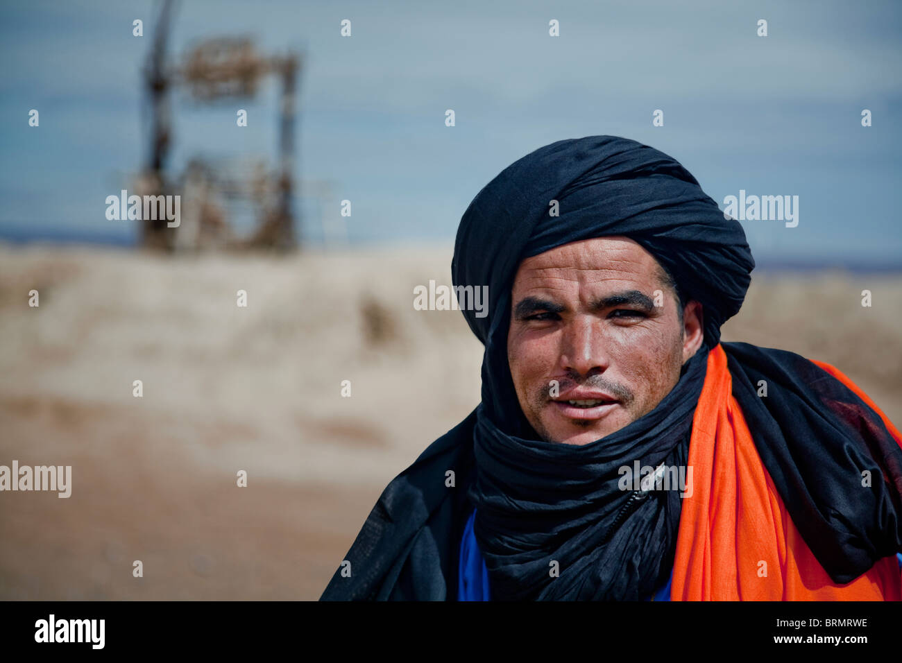 Portrait of a Berber man standing in front of an old well at a place of rest. - Stock Image