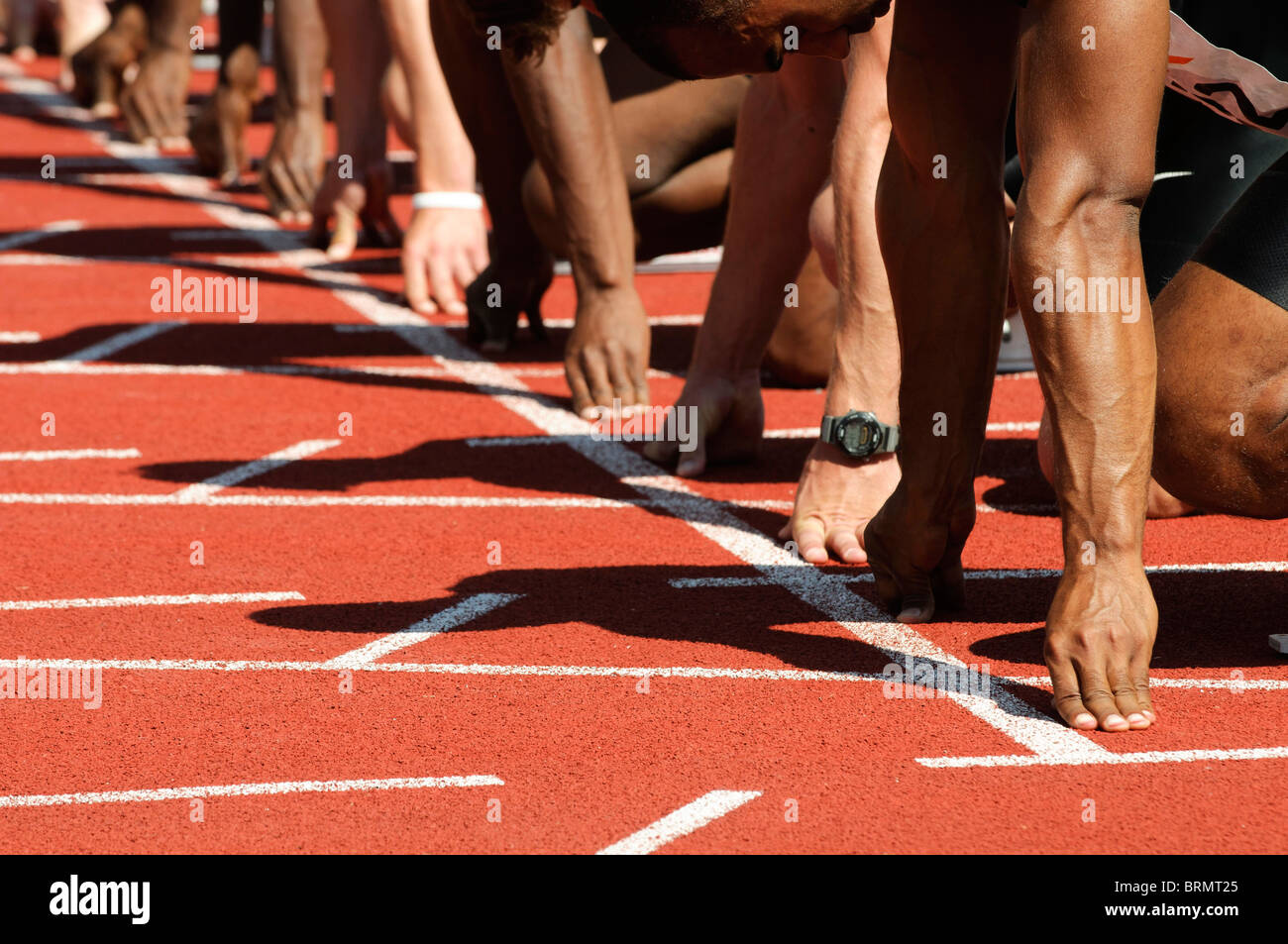 male sprinters line up  their hands on the starting line at track and field event - Stock Image
