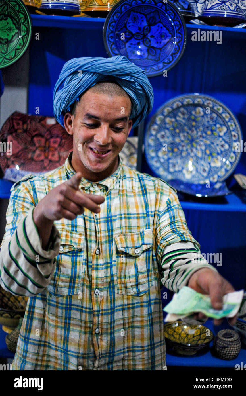 A portrait of a Moroccan shopkeeper with colourful ceramic bowls behind him holding out notes in his hand - Stock Image