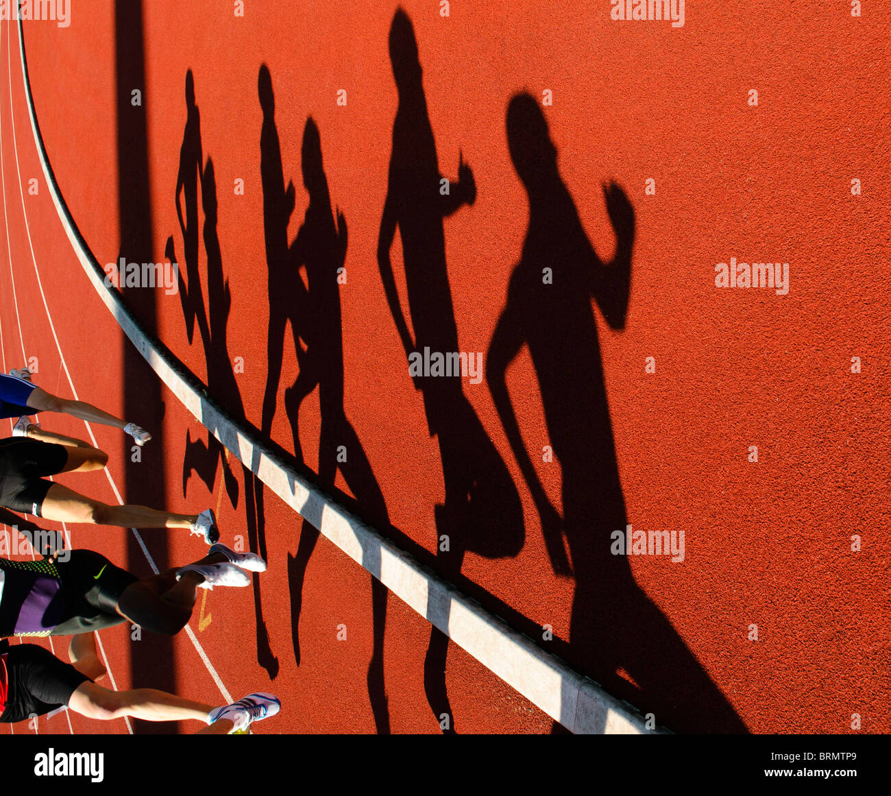 shadows of runners during 800m race during outdoor track and field competition Stock Photo