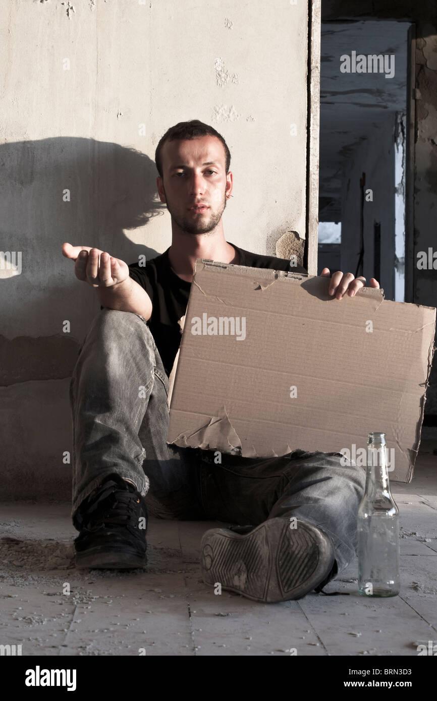 Beggar Sitting on the Floor - Stock Image