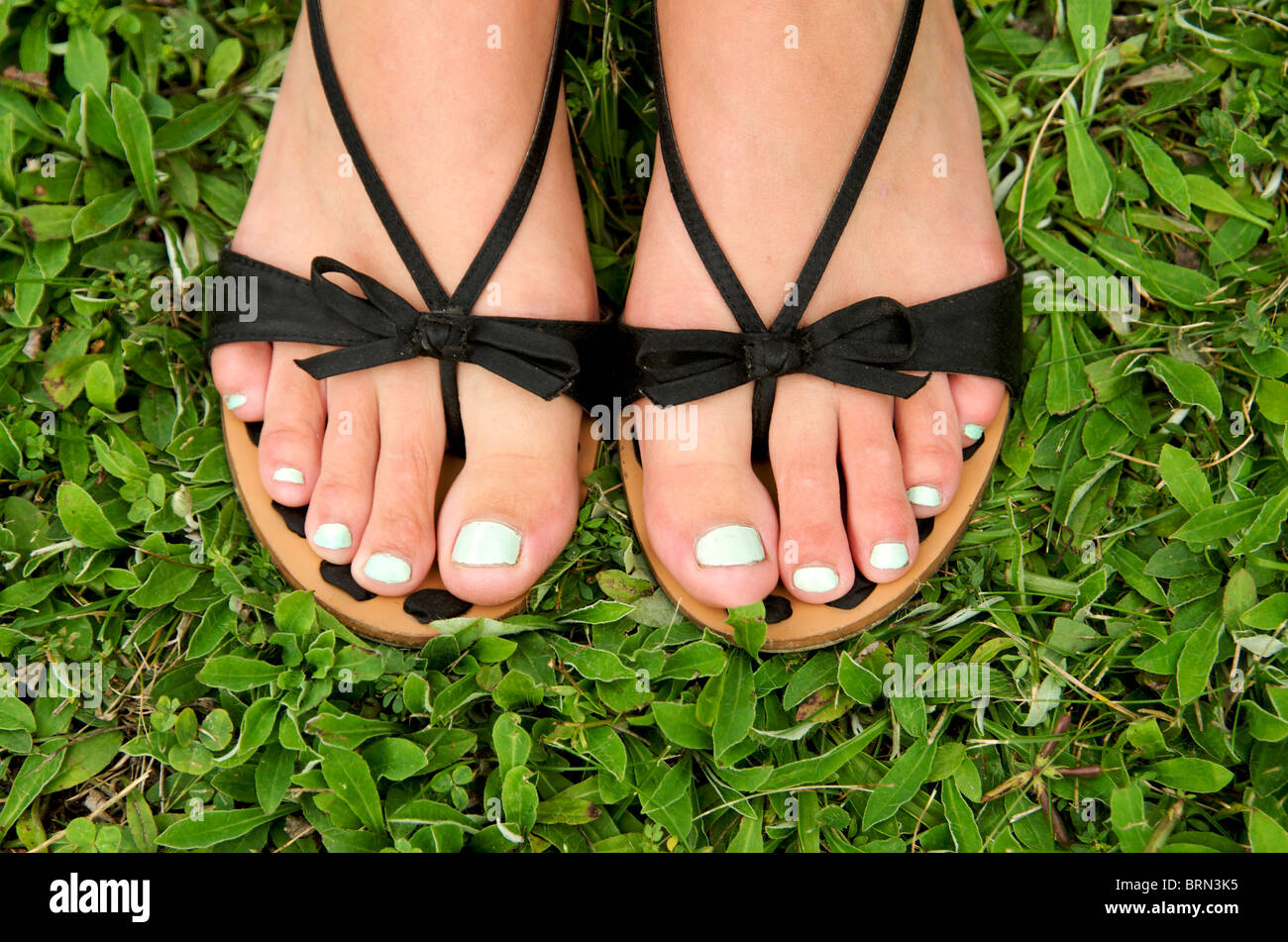 f98d208ee Close-up on the bare feet and varnished toe nails of a young woman -