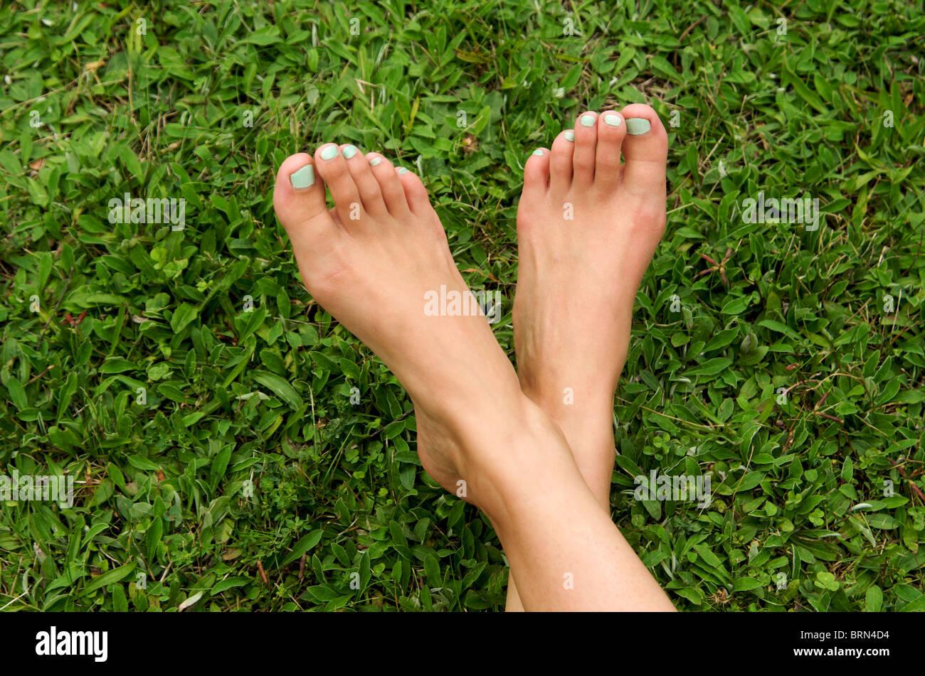 Feet and legs on grass outdoors - Stock Image