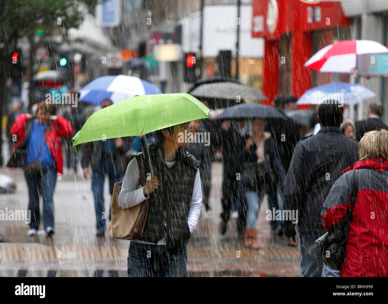 Shoppers on a cold and rainy day. - Stock Image