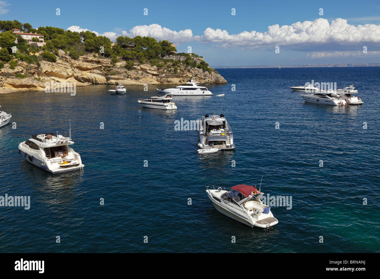 ESP Spain Balearic Mallorca Portals Vells bay boat rock water sea cloud sky blue idyllic idyl anchoring anchor sun - Stock Image