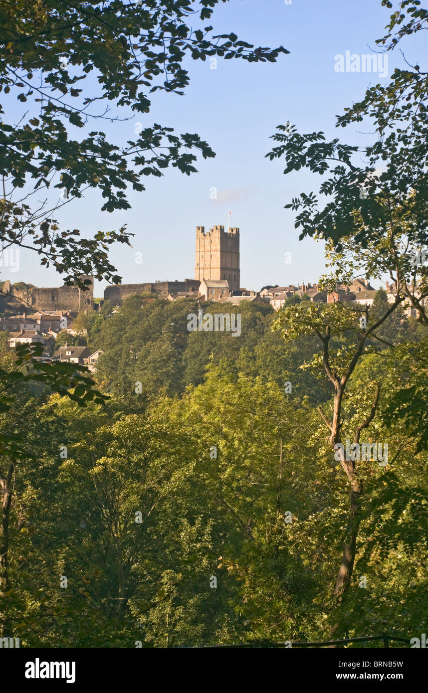 The castle and town of Richmond, North Yorkshire seen from the woodland walk to Easby Abbey. Stock Photo