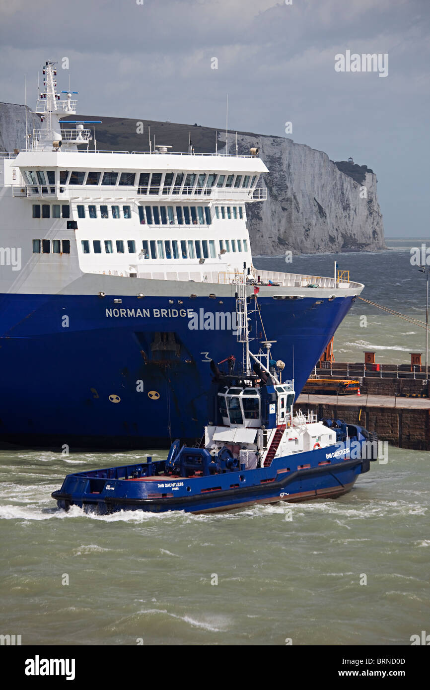 Tugboat pulling out LD Lines cross channel ferry the Norman Bridge from Dover harbour England UK - Stock Image