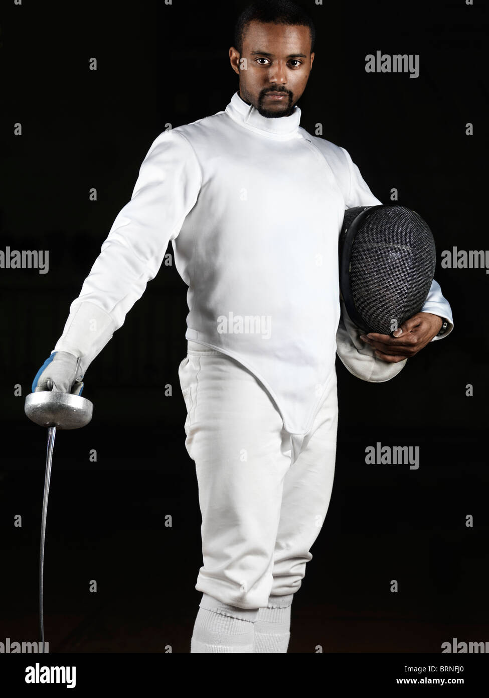 Portrait of a fencer wearing fencing uniform and holding an epee and a mask isolated on black background - Stock Image