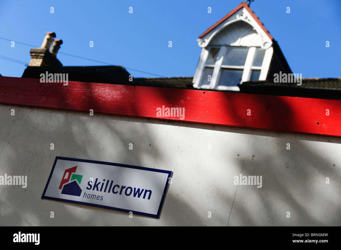 A site hoarding around a house bearing the name and logo of Skillcrown homes. - Stock Image