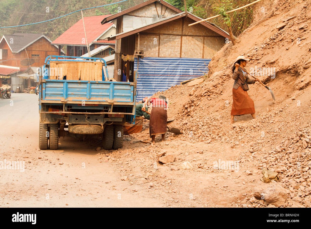 Two women wearing skirts shoveling dirt into a truck at a construction site in Laos - Stock Image