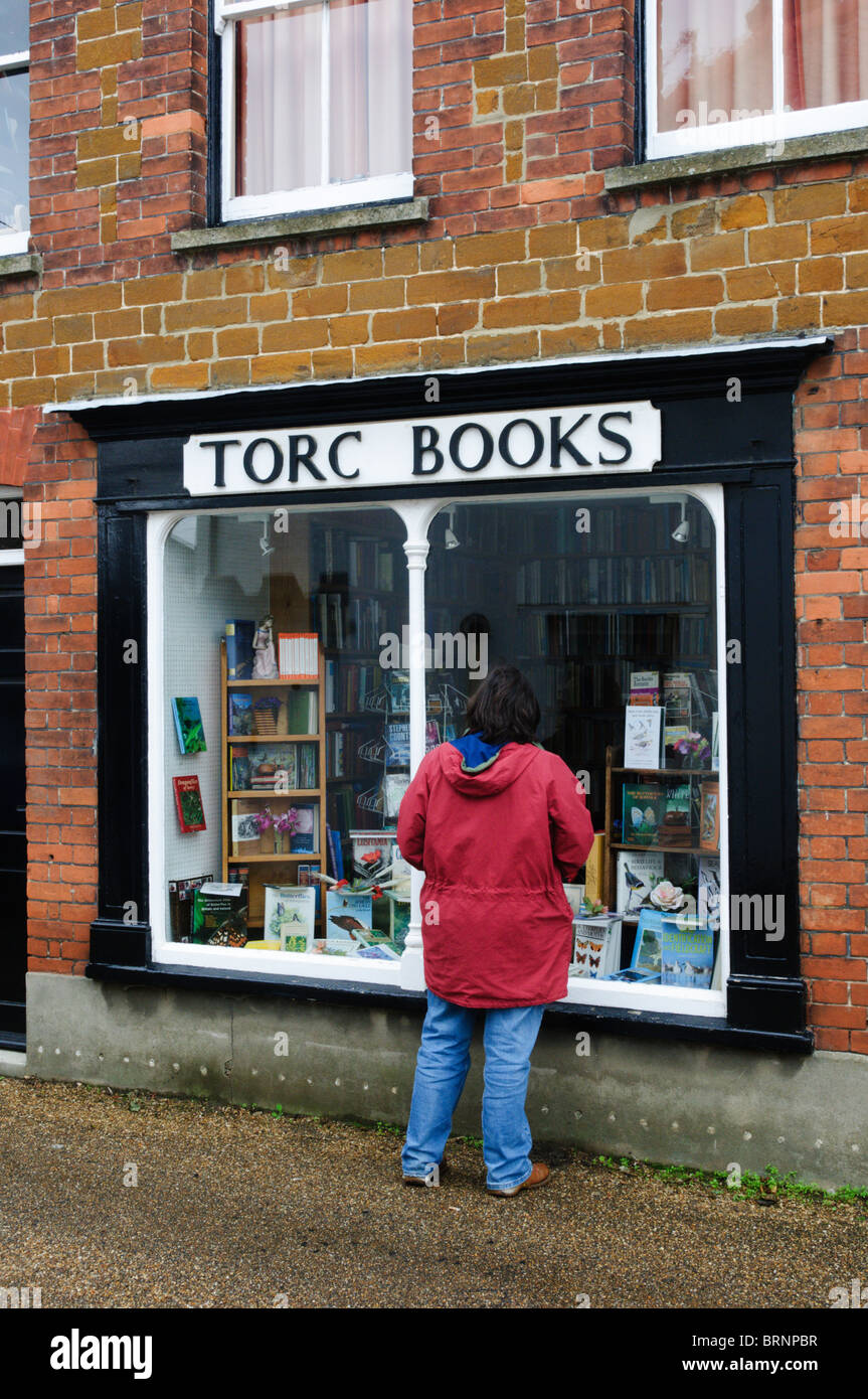 A woman looking in the window of Torc Books, a small secondhand bookshop in the village of Snettisham, Norfolk - Stock Image