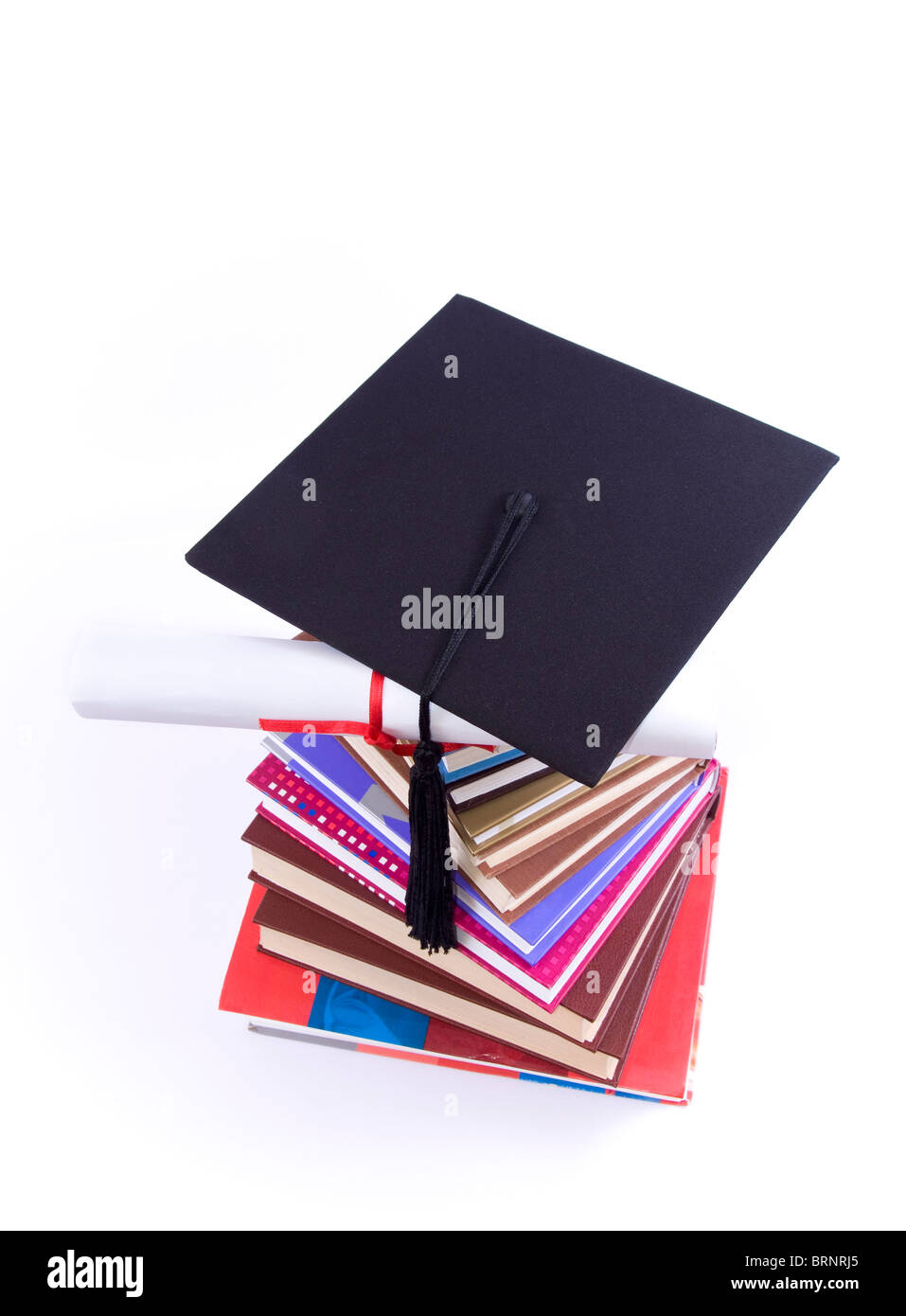 A lot of books, tower made of books with student hat and diploma, against a white background - Stock Image