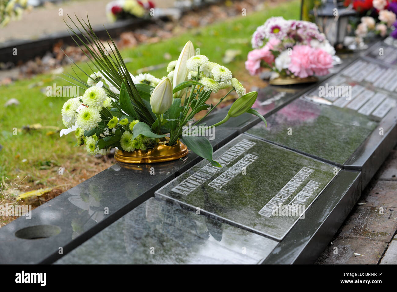 White lilies and flowers in a vase on a black marble kerbside memorial in a cemetery - Stock Image