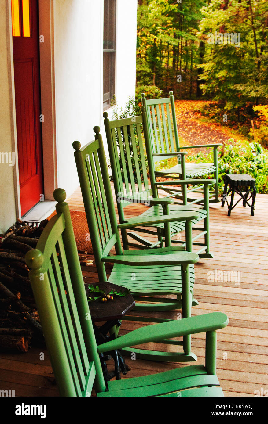 Green Rocking Chairs On Front Porch Of White Rural Farmhouse   Stock Image