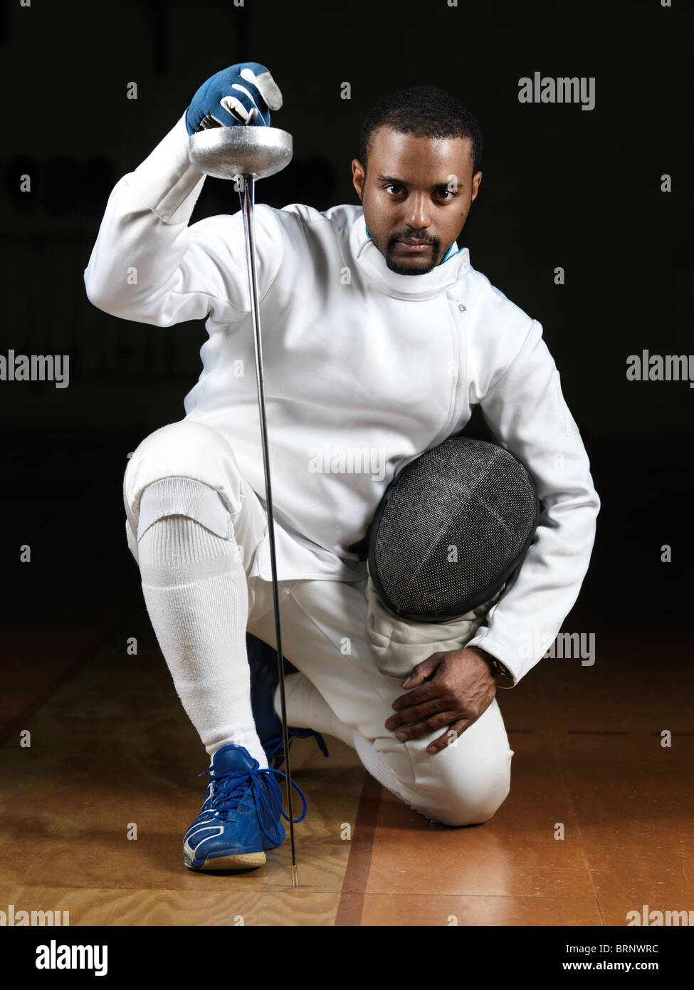 Portrait of a fencer wearing fencing uniform and holding an epee in a gym on black background - Stock Image