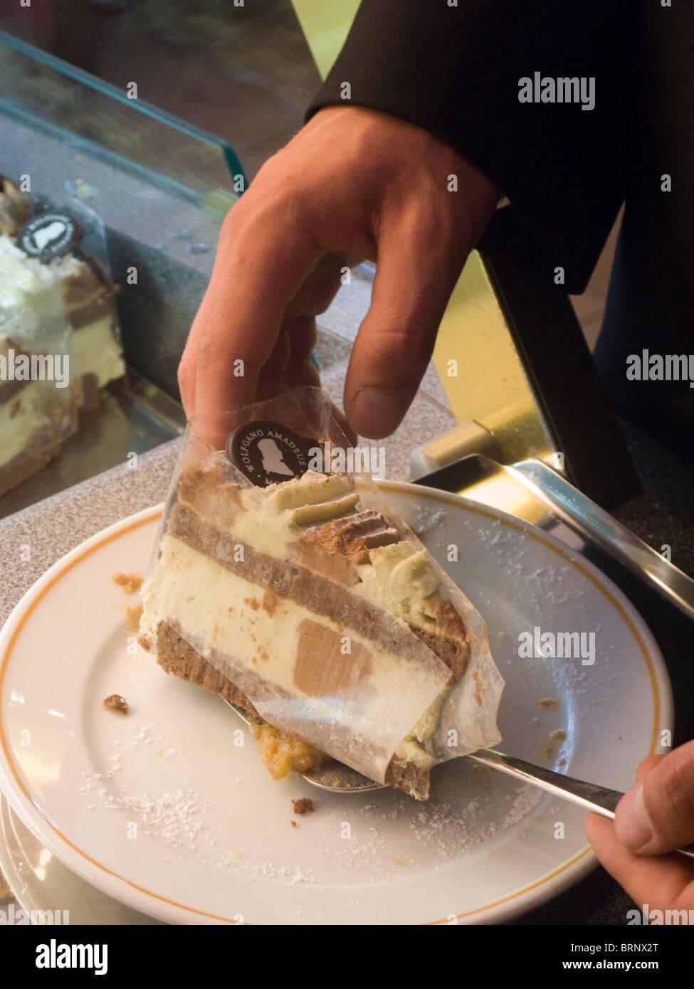 Waiter serving a delicious cake. Cafe Mozart, Vienna, Austria - Stock Image