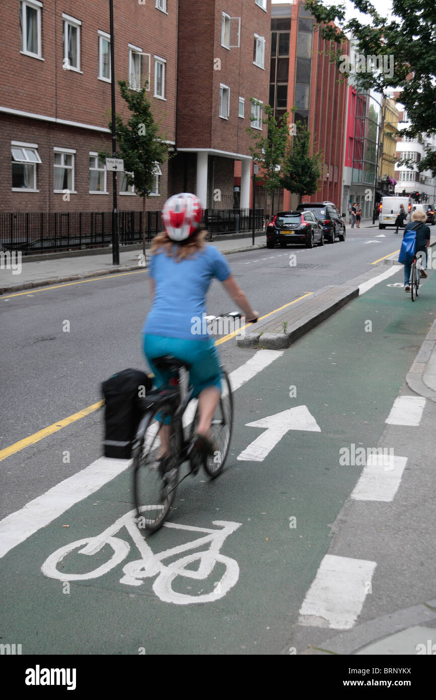 Female cyclist (blurry) cycling down a purpose build cycle lane on Howland Street (off Tottenham Court Road) London, - Stock Image