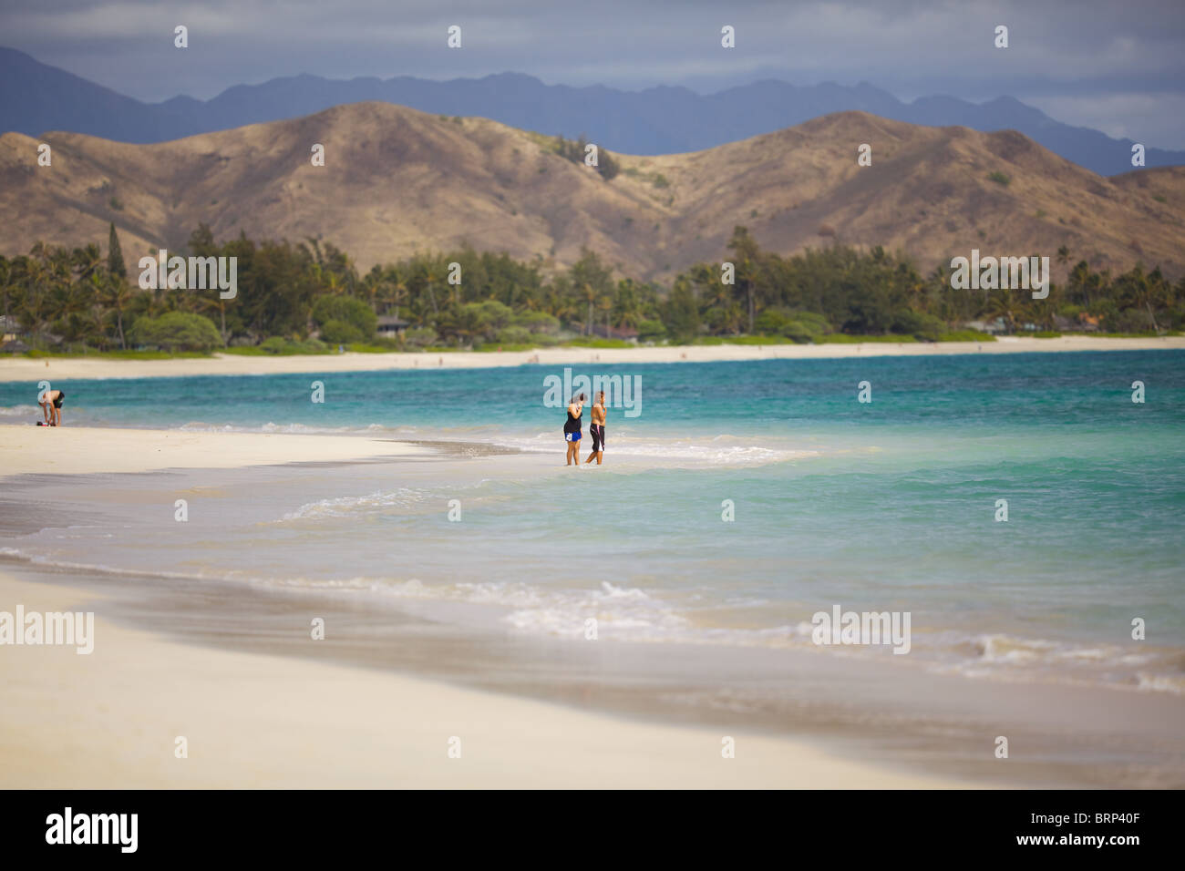 Two people stand by the edge of the ocean at Kailua Beach, Oahu, Hawaii - Stock Image