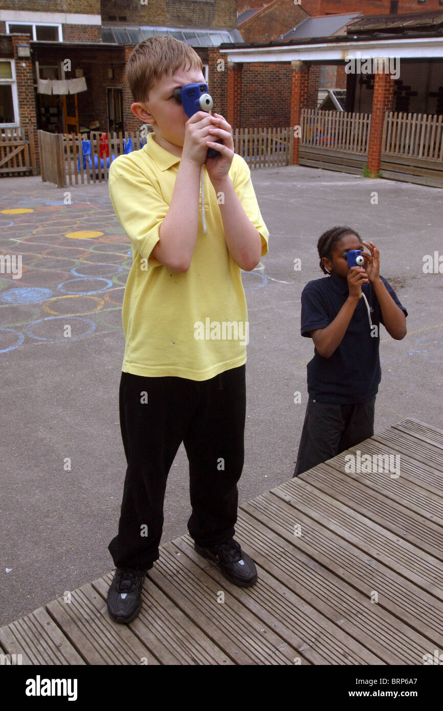 Secondary school children using surveying tool to measure buildings on school playground Stock Photo