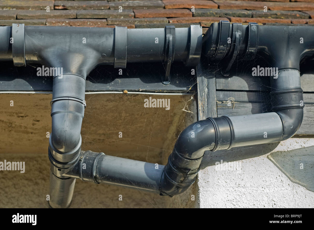 Guttering and drainage pipes on a house in poor condition. - Stock Image