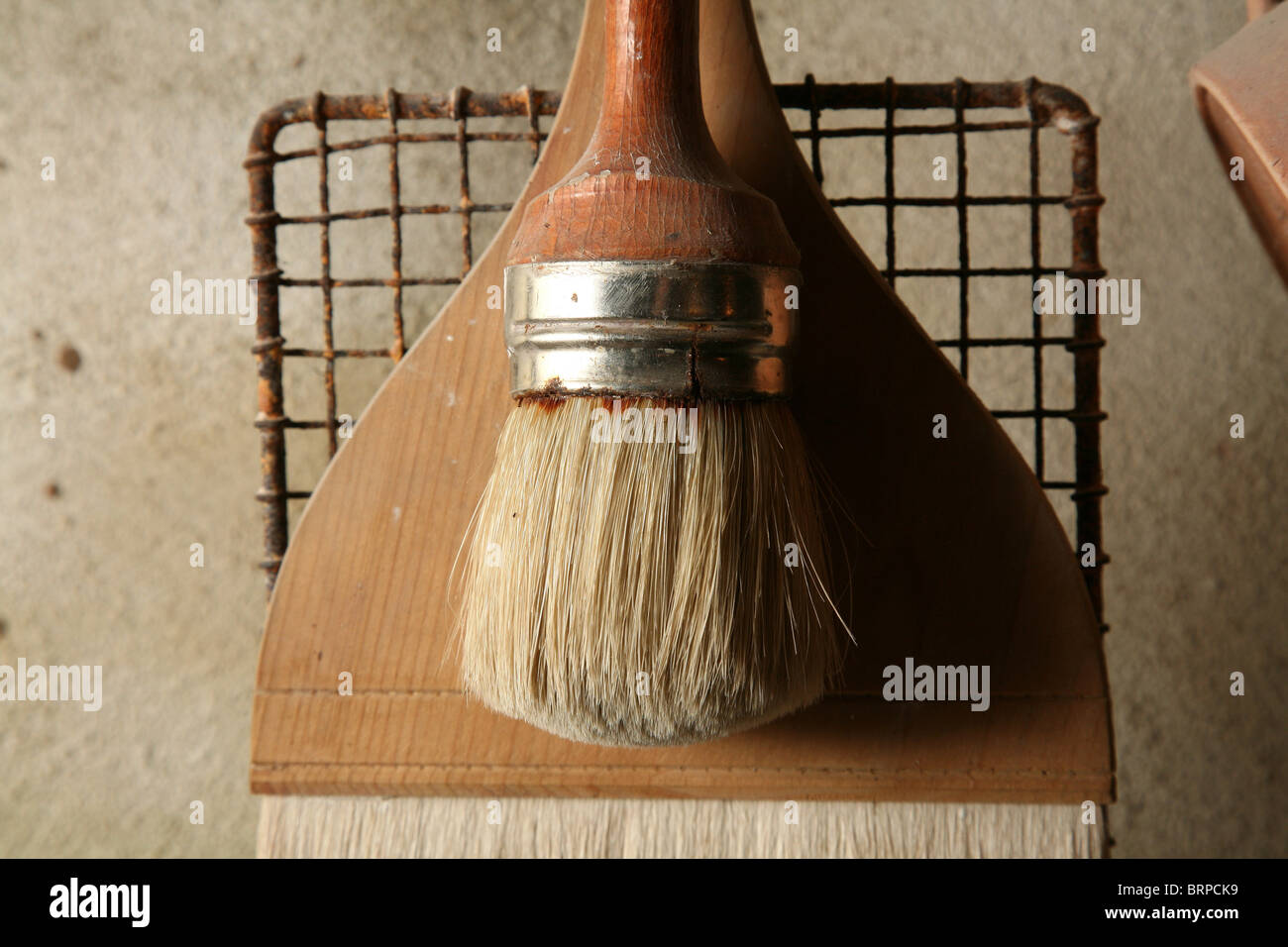 Two brushes in potter's studio on a wire grid background - Stock Image