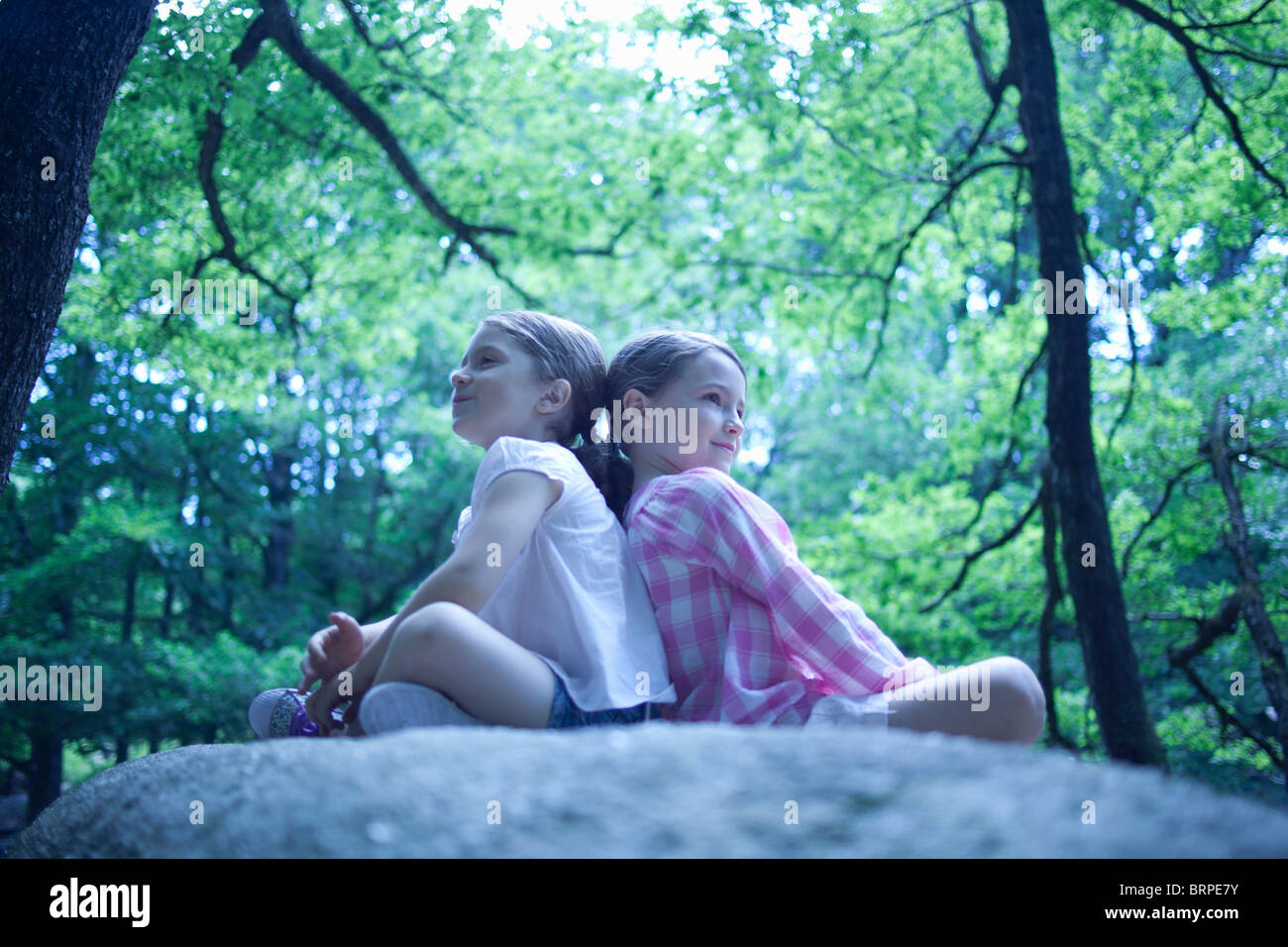 2 girls sitting on a big roc in forest - Stock Image