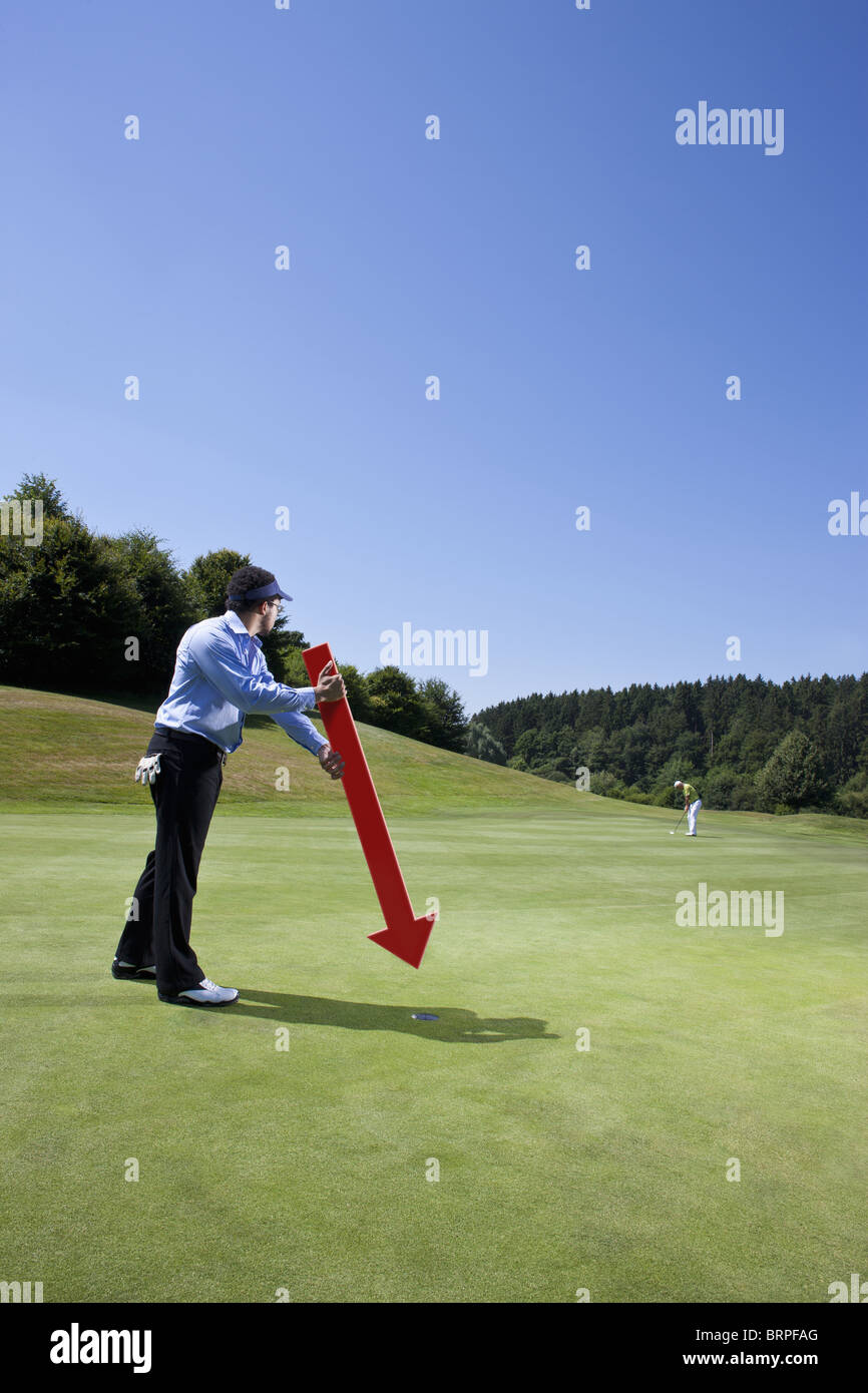 Caddy pointing at a hole on golf course Stock Photo