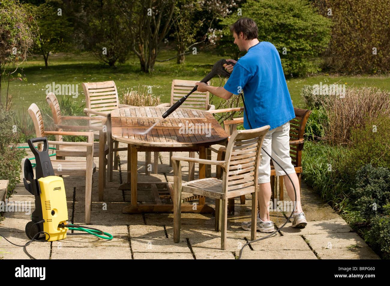 Man using a pressure washer to clean teak wood garden furniture - Man Using A Pressure Washer To Clean Teak Wood Garden Furniture