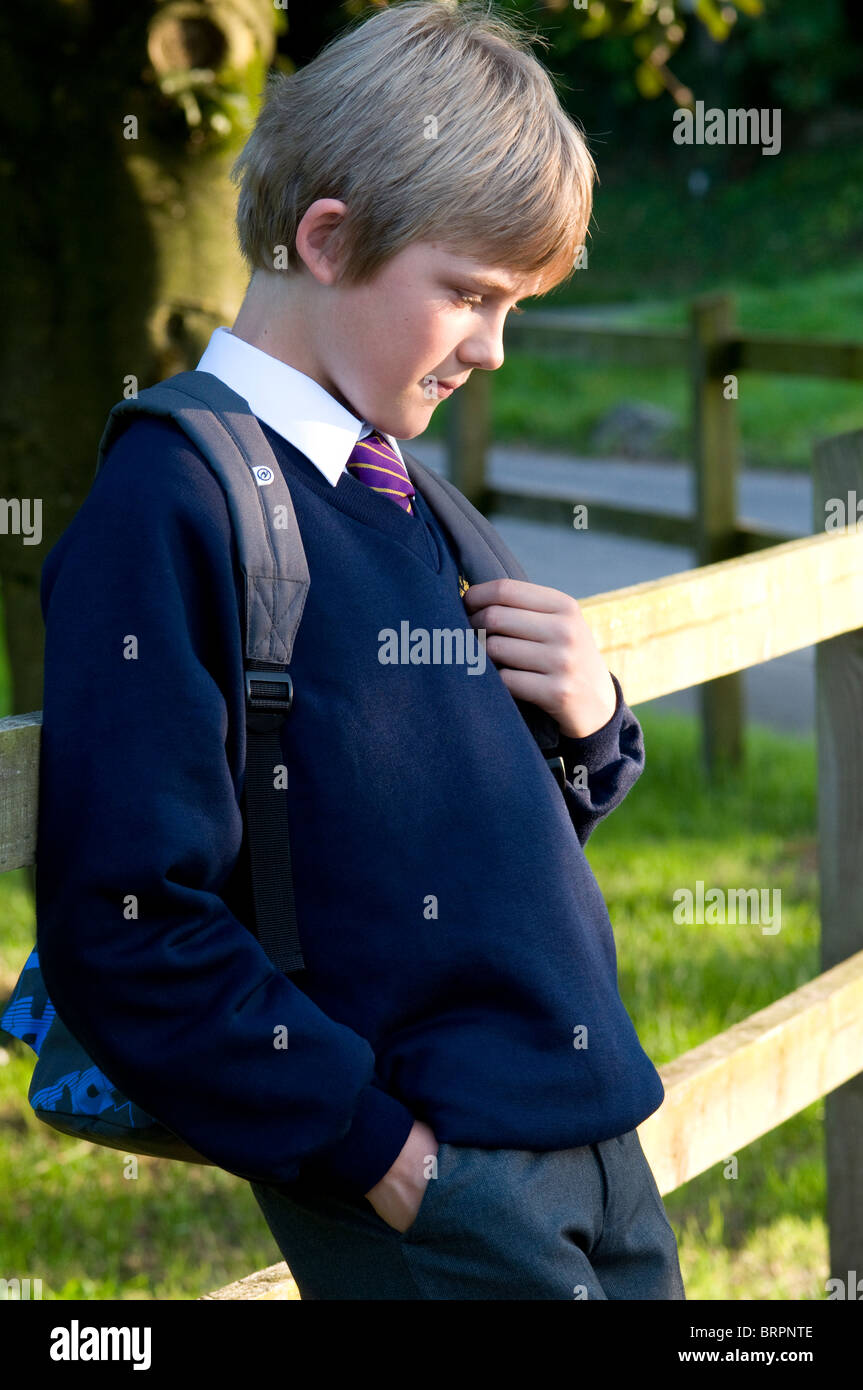 Schoolboy leaning on a fence looking slightly apprehensive - Stock Image