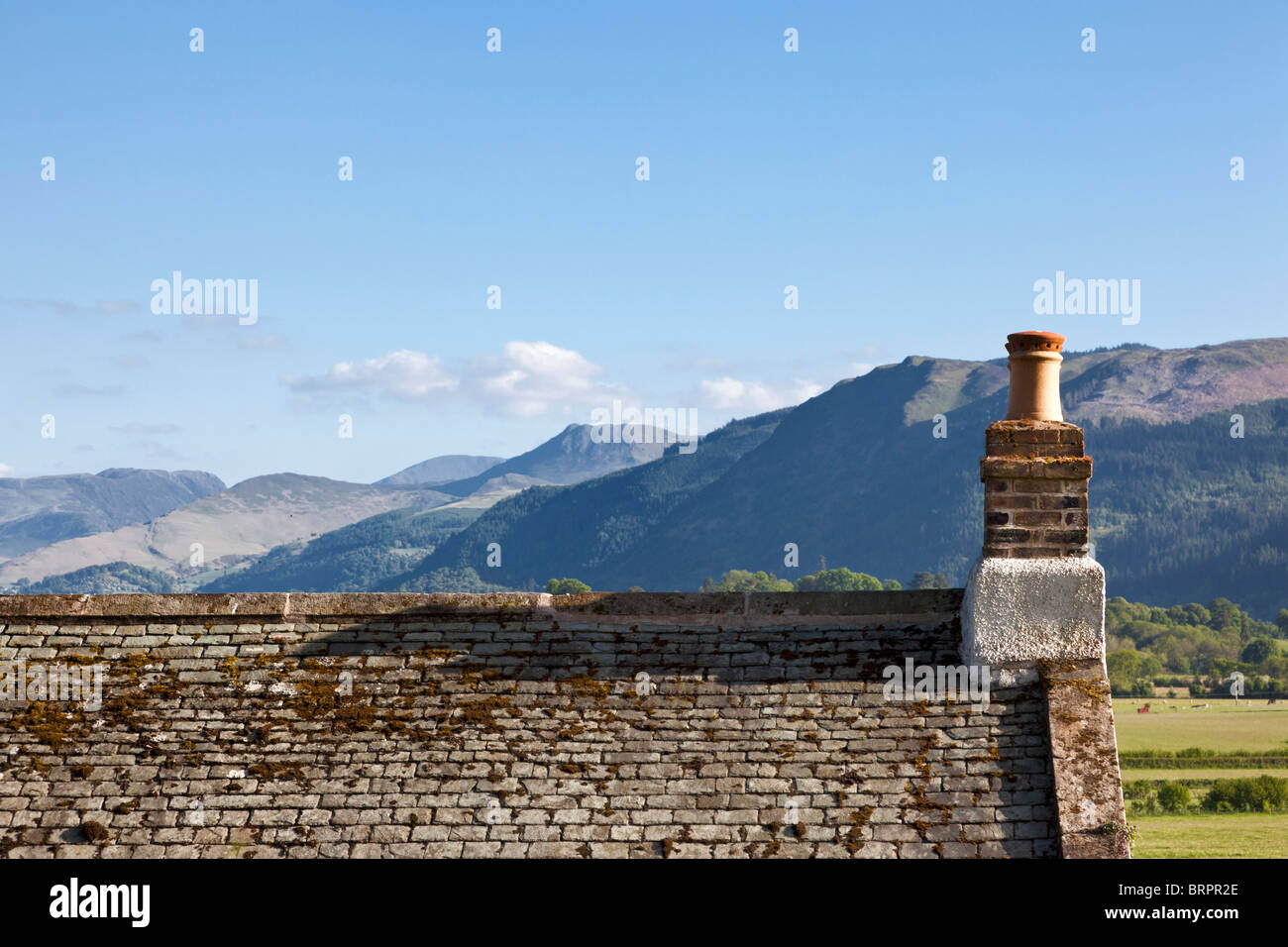 Old slate roof house roof and chimney overlooking mountains, Cumbria, England, UK - Stock Image