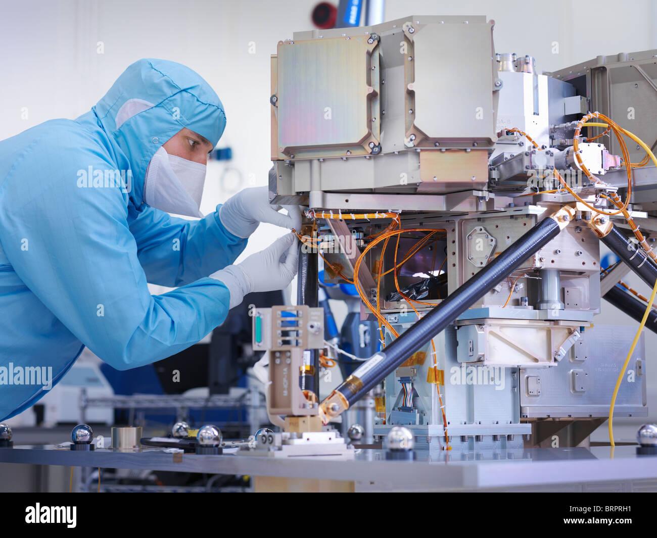 Worker building satellite dish - Stock Image