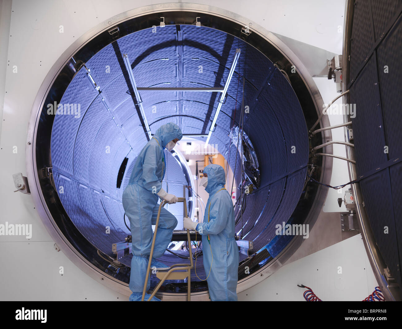 Workers with satellite testing chamber - Stock Image
