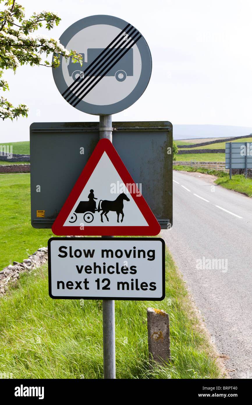 Sign on the A683 NE of Sedbergh, Cumbria warning of slow moving horse drawn vehicles travelling to the Appleby Horse - Stock Image