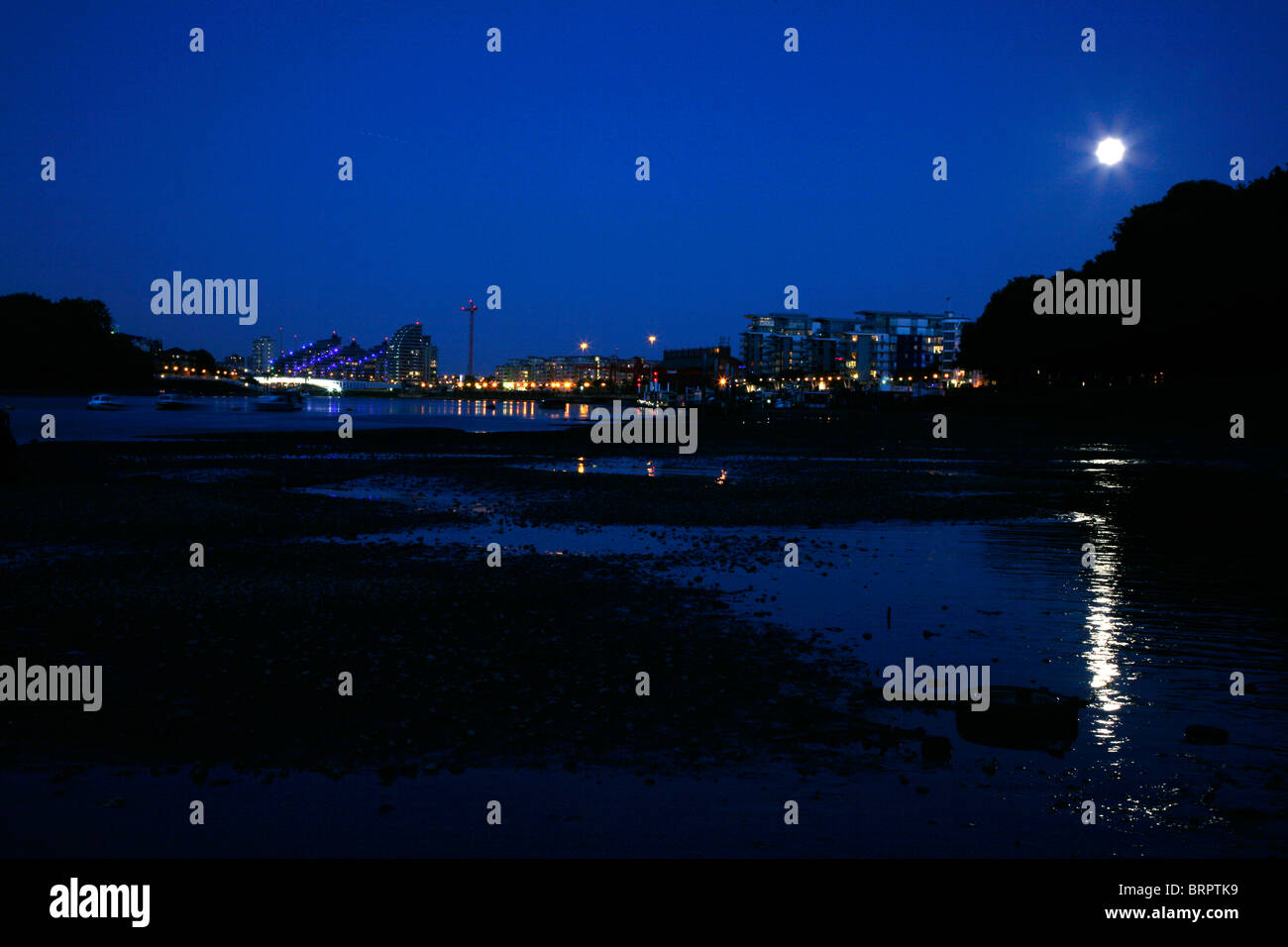 Full moon shining on the River Thames at low tide at Wandsworth, London, UK - Stock Image