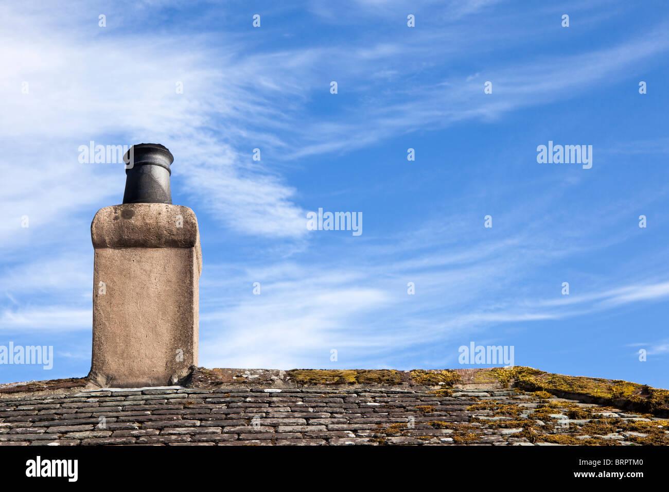 Old rendered chimney pot stack on a slate roof UK - Stock Image