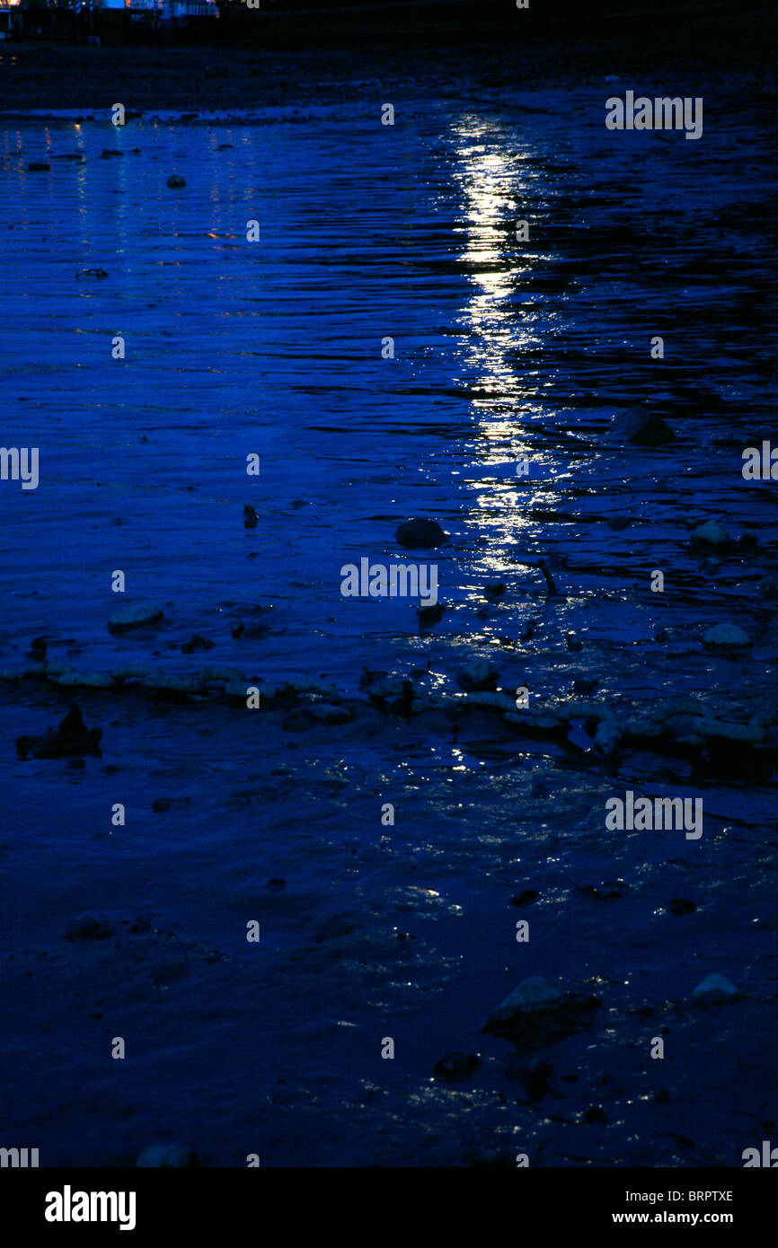 Full moon reflecting on the low tide mud on the River Thames at Wandsworth, London, UK - Stock Image