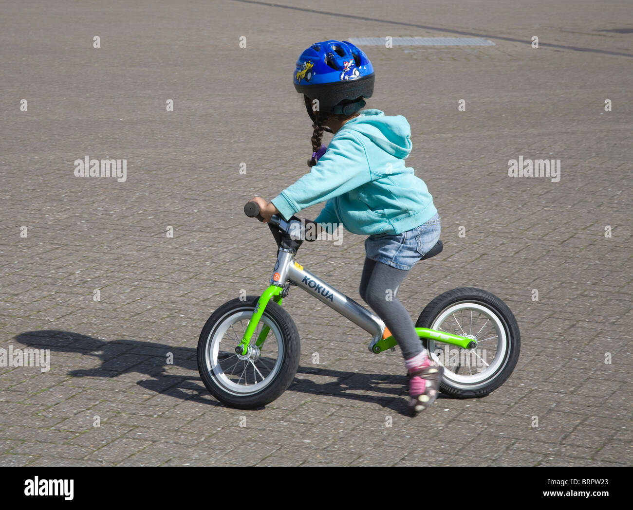 Close up little girl wearing a blue cycling helmet riding a small bicycle - Stock Image