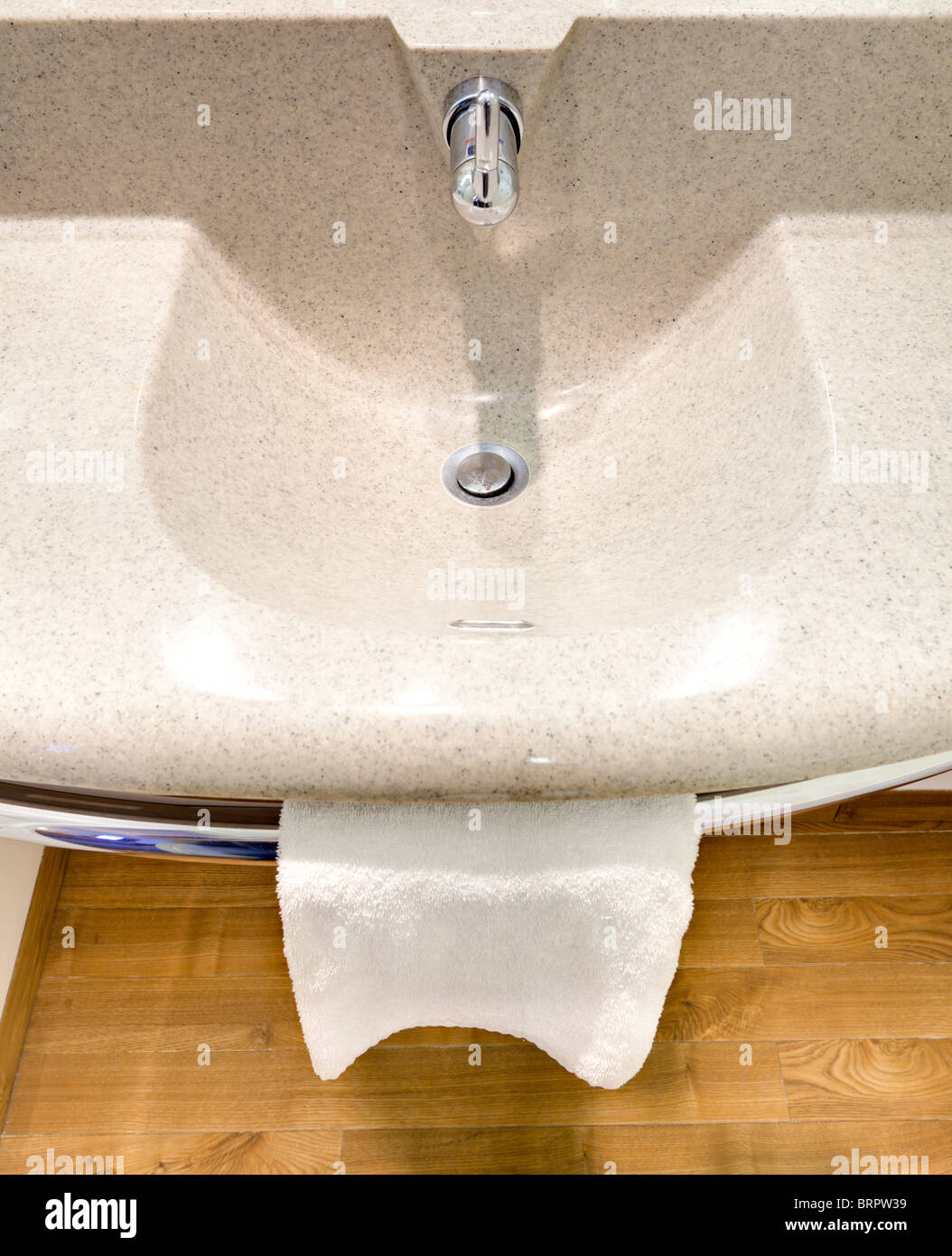 Sink tap and towel in a hotel bathroom - Stock Image