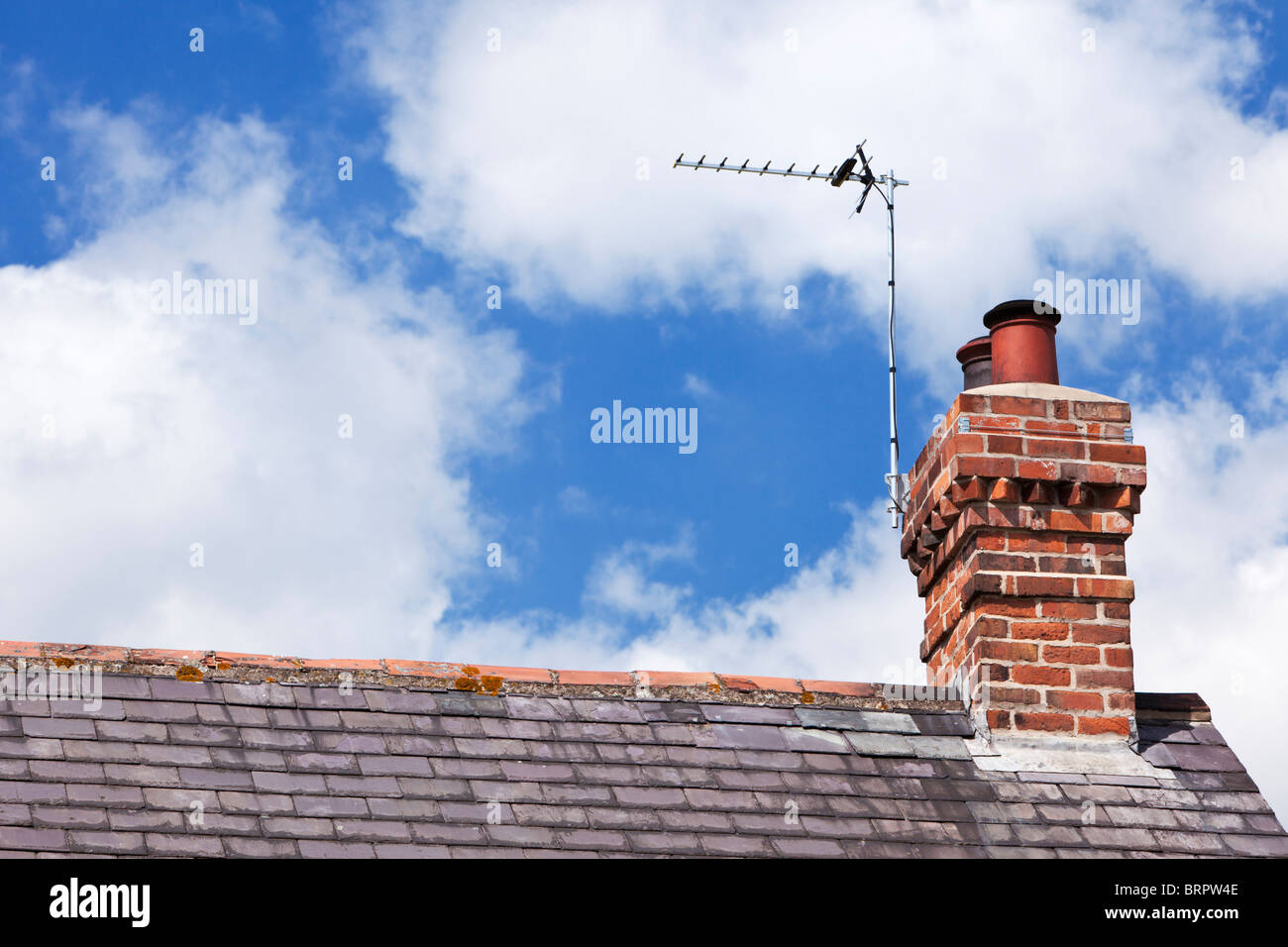 TV aerial on a house slate roof with red brick chimney stack UK - Stock Image