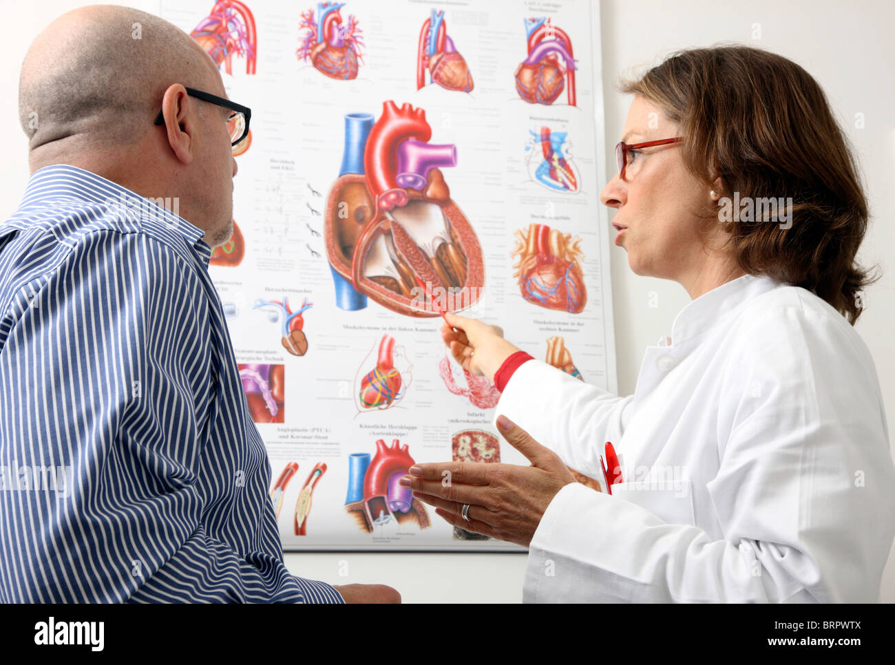 Doctors surgery, Female doctor explains the function and diseases of the human heart to a male patient. Consultation - Stock Image